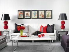 This white living room makes good use of carefully chosen wall art and red and black accents to create a distinctly Asian feel in the space. A white tufted leather sofa, marble-topped coffee table and glass end tables add contemporary touches.