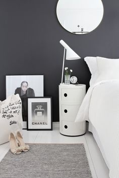 black wall + white bedding + circular mirror + layered frames + white floors + tote bag