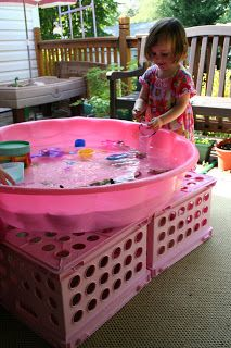 Make your own water table using a small pool and overturned crates--great way to get a larger-sized water table for several kids to use at once.