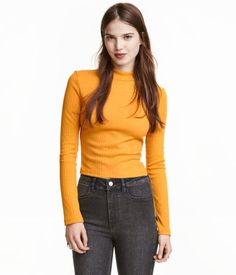 Mustard yellow. Short top in soft, ribbed jersey with a mock turtleneck and long sleeves.