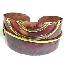 Handcrafted by South African artisans, this simple yet elegant copper cuff adorned with scrolls of polished brass is 1.25 inches wide and tapers at the ends. The random ruby-red color is achieved using high heat rather than paints or dyes.