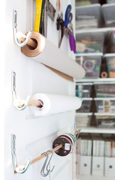 Paper / rolls - hung onto dowelling wooden rods (pipe would work too). The dowel/rod is then suspended from hooks - so the paper can roll off of the rod easily.