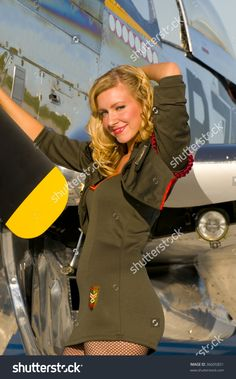 retro pinup girl in army uniform leaning on the wings of a world war two aircraft