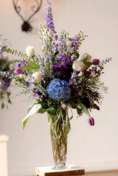 Elegant arrangement; would probably choose a different focus than the blue hydrangea in the middle.