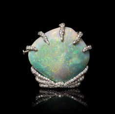 An 18 Karat White Gold, Opalized Clam Shell and Diamond Brooch, with 1.19 carats of round brilliant cut diamonds.