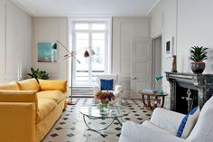 Comfy sofas and armchairs from British design star David Hicks in white and bright yellow contrast the Salon's marble floors. Note the pink stripes around the windows!