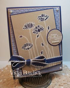 handmade card ... white embossing on craft with navy coloring in poppies ... like the way the ribbon matches the poppoies with white edges on navy ...