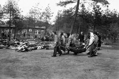 Liberated female inmates at Bergen-Belsen concentration camp carry a corpse from one of the huts toward a pile of bodies lying in the open in front of Block 210 (Großes Frauenlager). Bergen-Belsen concentration camp, Lower Saxony, Germany. 17 April 1945