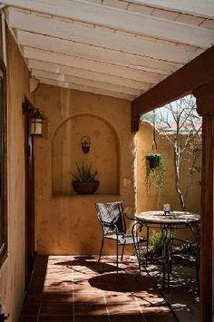 patio/pergola van bamboe met wilgenteen of...golfplaten? met druifrank. spaanse/terrakleur terrastegels witte muren of gelig?