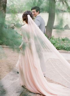 """The luxurious """" La Vie En Rose """" gown is made from 100% silk tulle. The skirt is fully lined and features a long flowing train. This gown has the most heavenly drape and flows like water. The french lace top is fully lined and shows off a v plunge neckline. Color: Morganite ( Blush ) by Emily Riggs Bridal"""