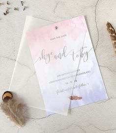 Feather // Luxury wedding save the dates with a serenity blue and rose quartz pink watercolour ombre design, watercolour feathers, calligraphy and a swing vellum cover. Perfect for a bohemian wedding in the country.