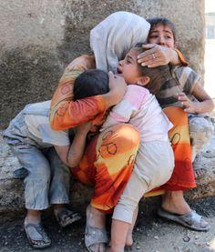 Seorang Ibu menenangkan ke-3 puteranya setelah rumah mereka di kota Aleppo hancur akibat serangan bom dari pasukan Suriah.