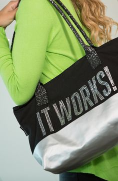 """BLING TOTE- Make an It Works! style statement wherever you go with this blinged out tote! Our canvas tote has a sturdy metallic coated bottom that offers a more structured feel. Black cork handles are a fashion forward touch with silver metallic flecks and best of all, """"It Works!"""" is front and centre in rhinestone studded bling! Versatile and fashionable, it's the perfect accessory for a Wrap Party or a night on the town!"""