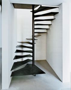 Calder Foundation project space by   STEPHANIEGOTO. New York, New York. Inserted in a narrow space between two of the old sheds, a spiral stair leads to a small office for the foundation's president. Treads of 3/8-inch-thick blackened steel are attached to a 4-inch-wide steel post and perimeter walls, creating a sense of movement.