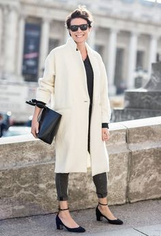 Garance Doré wears a black button-down shirt, white coat, cuffed jeans, and Valentino heels