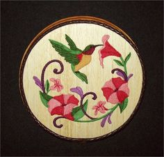 This unique Hummingbird Embroidery Wood Art, Bird Wall Decor combines the warmth of wood with the raised texture of 9 different thread colors and 32,322 stitches. The design was machine embroidered into a sheet of balsa wood, then cut and mounted on an oak stained 6-3/4 wide x 1 plaque. The brown leather braided trim was added before a clear protective, non-yellowing acrylic matte finish was applied. A brass hanger is attached to the backside making it ready for hanging.    Balsa Wood Em...