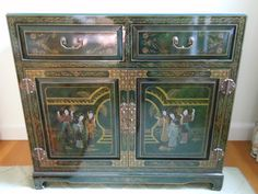 An iconic black oriental cabinet with figural decorations.