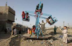 Pakistani children enjoy swings in the slums of Karachi, Pakistan. (Photo: Fareed Khan / Associated Press   Boston Globe   The Big Picture   Daily life: March 2012)