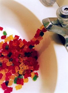 Writing Prompt. Describe what is happening in the picture? Tell a story about why Gummi Bears are coming out of the sink.
