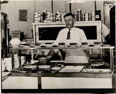 """Louis DeHatre stands behind the counter of his diner, """"Louie's Place,"""" at the St. Louis Municipal Flying Field, later named Lambert Field. DeHatre ran """"Louie's Place"""" in the late 1920s and early 1930s. He collected and displayed photographs of his aviator patrons and their aircrafts. Missouri History Museum"""