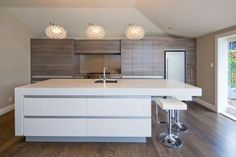 The design pairs a white-lacquered island and a CaesarStone Snow benchtop with Laminex Lustrous Elm laminate cabinetry. The 120mm-deep benchtop on the island reinforces its sense of solidity and permanence. www.thelaminexgroup.co.nz