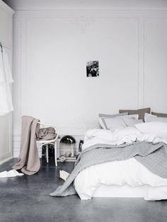 Bedroom: grey polished concrete floor, white and grey bedlinen, high ceilings…