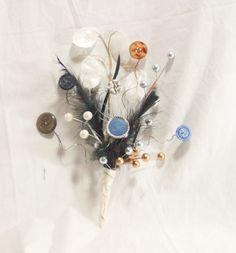 DIY button/feather bouquets! Love the idea of found objects vs live or fake flowers.