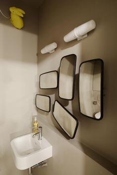 A collection of large rear view mirrors salvaged from industrial shipping trucks makes up the bathroom mirror. The sink is the Ideal Standard Concept Cube Washbasin.