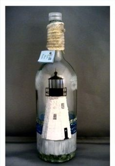 """Handpainted Lighthouse on a 11"""" high x 4.5"""" diameter wine bottle. This bottle can be made with your choice of lighthouse. Led light on top gives bottle a soft glow at night. 35.99"""