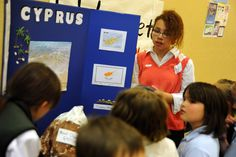"""Fifth grader Kelsey Brown, 11, explains Cyprus landmarks for second graders May 10 at Banning Lewis Ranch Academy in Falcon School District 49. While kindergarten-fourth grade students entered the academy's gymnasium, groups of fifth graders welcomed them to """"European extravaganza."""" They encouraged them to visit their country-themed tables, where they'd present research and stamp """"passports."""" The daylong event started with classroom presentations of slideshows and magazine projects."""