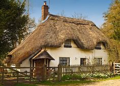 A white cottage with a thatched roof surrounded by flowers Storybook Homes, Storybook Cottage, Thatched House, Thatched Roof, Fairytale Cottage, Garden Cottage, English Country Cottages, English Countryside, Country Houses