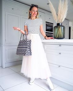 Casual outfit idea - tee, pleated skirt and sneakers | For more style inspiration visit 40plusstyle.com