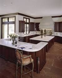 Deep reddish brown marble flooring is paired with darker wood cabinetry under white marble countertops and white walls in this open, minimalist kitchen. Contemporary Kitchen Cabinets, Wood Kitchen Cabinets, Kitchen Flooring, Kitchen Countertops, Marble Countertops, Copper Backsplash, Pantry Cabinets, Backsplash Ideas, Kitchen Pantry