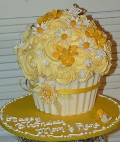 """This is a lemon cake made with the Wilton's Giant Cupcake pan.  I've really wanted to make this cake, as I've seen other beautiful examples here on CC. This is a lemon cake frosted in buttercream  with fondant flowers and butterflies.  The cupcake """"cup"""" is white chocolate and I trimmed the cake to fit inside of it.  Thanks for looking!"""