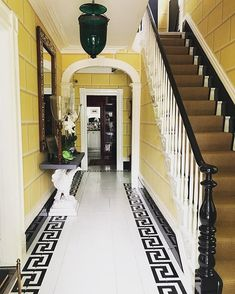 Sag Harbor Home by Nick Olsen painted black and white floors with greek key trim, entry hall foyer