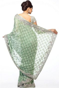 Sap Green Woven Saree with Silver Floral Motif Swarovski scattered throughout. Borders with traditional floral motifs embellished with silver synthetic crystal, Swarovski & Pipe Sequins.