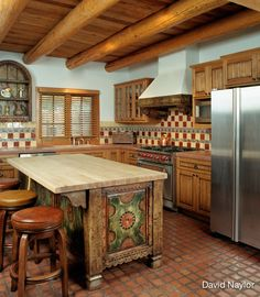 In this kitchen, the island's design was inspired by an old New Mexican trunk that was on display at the Museum of International Folk Art in Santa Fe. We also carved the range hood to match the trunk; the floor is made of polished concrete squares, rubbed with pigment to look like leather.