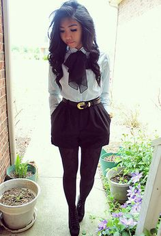 love the pinstripe shirt tucked into chic black belted shorts (and the bow adds just the right amount of dramatic)