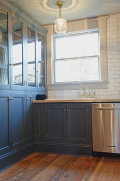Chic Design Investments:  Modernized foursquare kitchen sink nook.  Black cabinets, subway tile, brass and wood.
