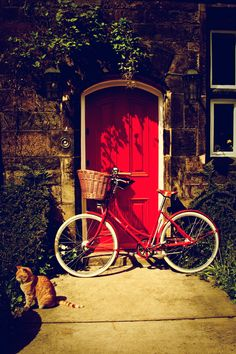 A lovely Pashley Cycle (England's longest established bicycle manufacturer founded in 1926) and a Ginger Moggy are parked in front of this inviting red cottage door.