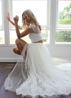 If you want to take the crop top trend up a notch, this modern wedding dress features an illusion lace topper over a strapless tank and a full tulle skirt with a thigh-high slit.