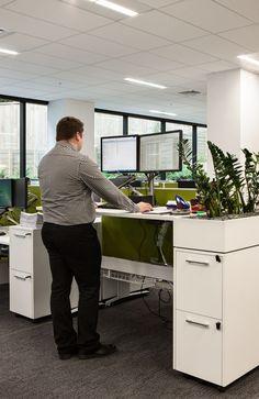 Height adjustable desk between storage