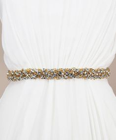 """Transform the simplest of outfits with a dramatic crystal embellished sash.• Austrian crystals - round cut • Gold glass beading • 18"""" x 1"""" • Hand sewn onto a ribbon in the color of your choice • Ribbon closure allows for universal sizing • Pictured on white sheer organza ribbonExtended beading available, contact us at shop@kirstenkuehndesigns.com for more information.Please allow 3-4 weeks production time for US orders"""