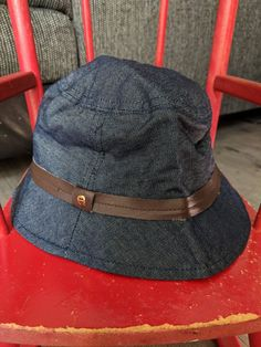 1e83257b359 Straight from the this designer Etienne Aigner hat is vintage fun! The  denim hat has a leather strap around it and metallic Etienne Aigner symbol.