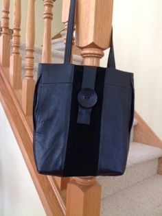 Black bag made from recycled leather and suede found at a local thrift store.  It has 3 inside pockets and closes with the large button. Two side pockets add places to slip cell phone and keys.