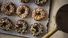Suklaakuorrutteiset donitsit koristeellaan pistaasi- ja hasselpähkinärouheella.