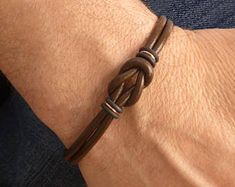 This mens brown leather bracelet in the style of a Celtic bracelet, is made from genuine rich brown leather cord and quality metal cast antiqued copper Zamak hardware. A hypoallergenic, certified lead and nickel free unisex bracelet that closes with a sle Celtic Bracelet, Copper Bracelet, Braided Bracelets, Bracelets For Men, Bracelet Couple, Cordon En Cuir, Bijoux Fil Aluminium, Ring Der O, Unique Gifts For Men