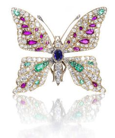 A diamond and gem-set butterfly brooch late 19th/early 20th century - The head, thorax & abdomen set with an oval-cut sapphire & cushion-shaped diamonds, the eyes with cabochon rubies, the wings pavé-set with old brilliant, cushion, single & rose-cut diamonds, & vari-cut emeralds & rubies, the antennae with rose-cut diamond tips, the legs & abdomen with engraved decoration, mounted in yellow gold, diamonds approximately 4.50 carats total, French assay marks, length at longest point 5.0cm