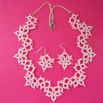 This soft pink necklace gently frames the neck with elegant swirls of loops and chains. It fastens on a silver chain with a lobster clasp.  The necklace measures about 17 1/2 inches long.  Matching earrings dangle 1 inch from silver colored ear wires.  For health reasons, once worn, this it...