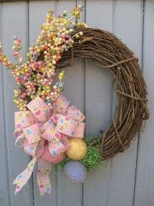"Etsy Easter Egg Wreath:  ""The finished size is approximately 16"" wide by 19"" long by 6"" deep. We started with a grapevine wreath base and nested faux crystal-covered easter eggs on a bed of green grass then accented them with pastel berry sprays and a beautiful Easter-themed bow."""